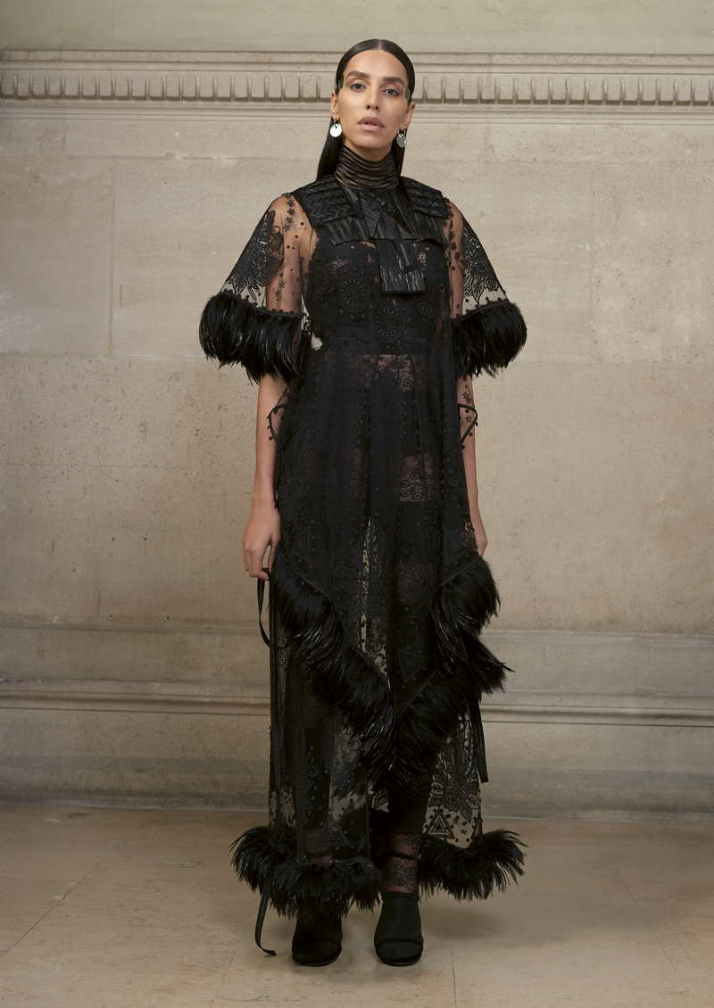 LEA T Long dress in black illusion tulle embroidered with delicate geometric floral motifs, a cut and glued feathered front, and ribbons of black rooster feathers at the sleeves and hem. + jumpsuit made in stripes of jersey and lace with lace incrusted