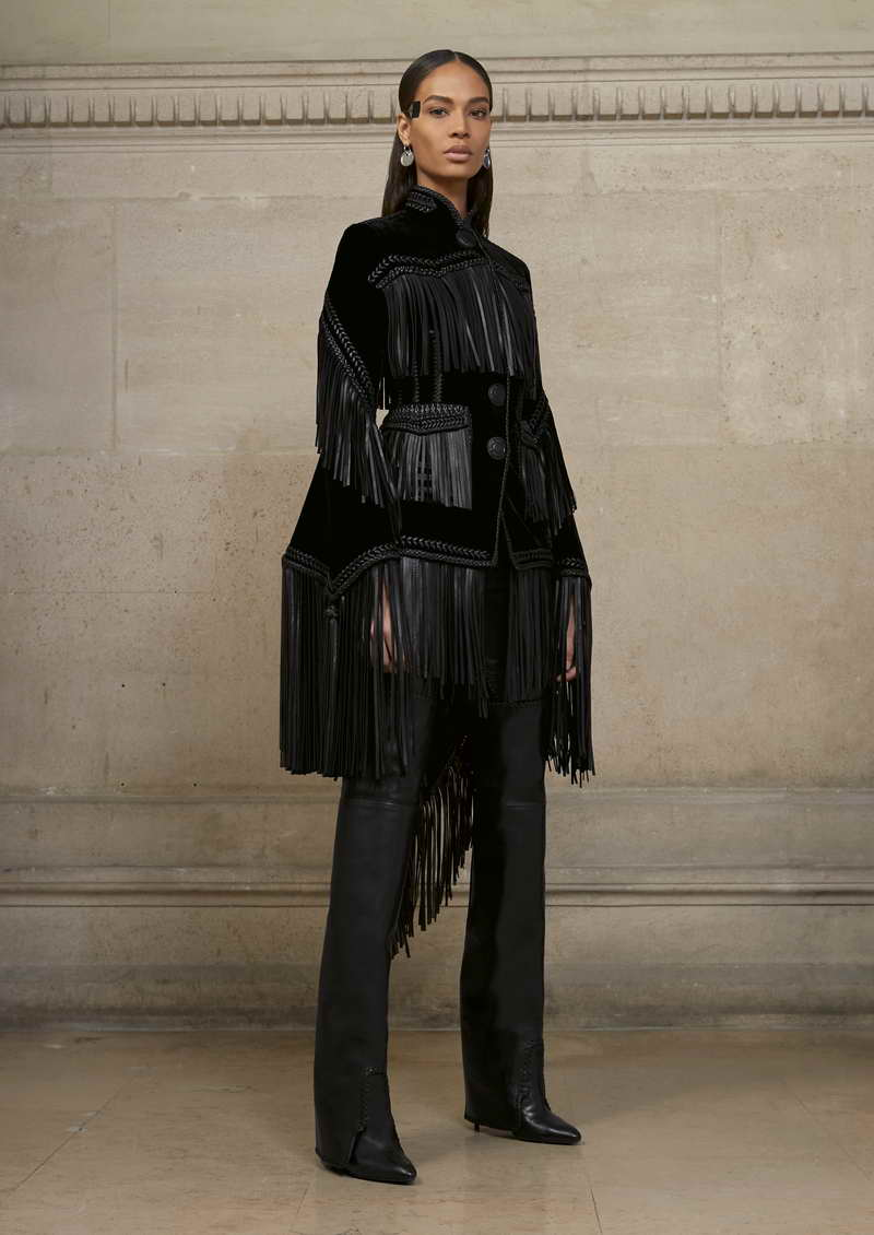 JOAN Tailcoat jacket in boned velvet decorated with leather fringes and leather interlacing. Stirrup pants in stretch washed lambskin leather with handwoven leather tie.