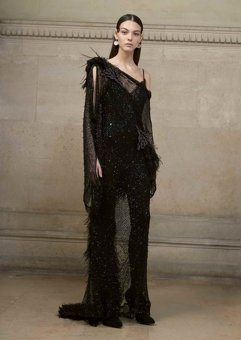 VITTORIA Long asymmetric dress in micro sequin mesh, embellished with ostrich, emu, and black heron feathers, as well as a composition of black mirror-effect crystals. + jersey and lace jumpsuit with lace incrusted