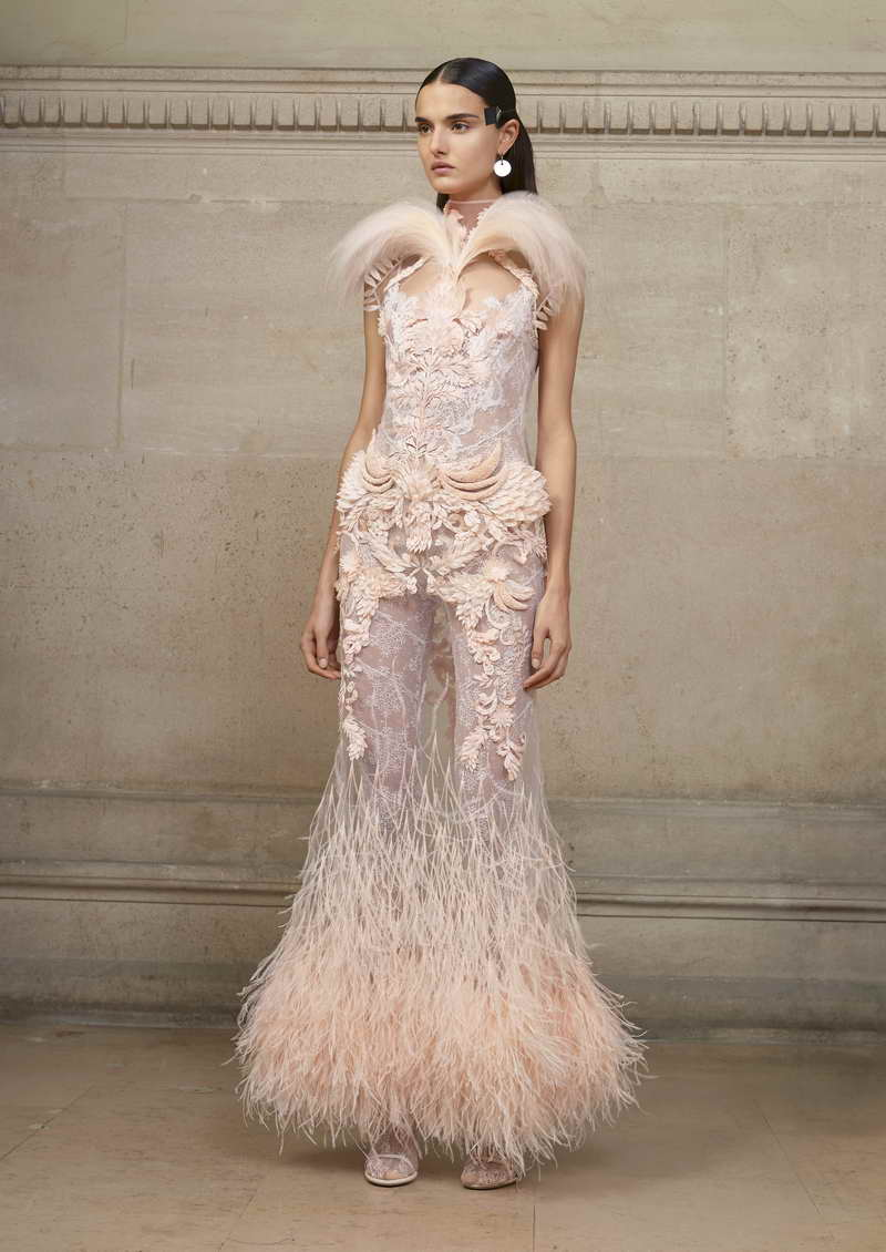 BLANCA Long dress in nude illusion tulle embellished with rooster feathers, cut feathers, ostrich feathers, and pink bird of paradise feathers. + patchwork of lace jumpsuit and lace incrusted