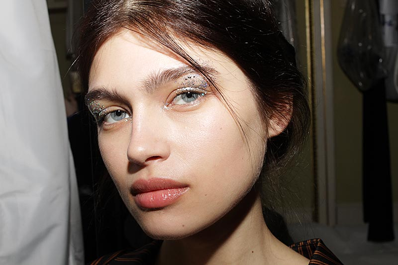 Make-up at Genny FW 2018 2019. Glitter eyes and a beautiful skin. Make-up: Lloyd Simmonds